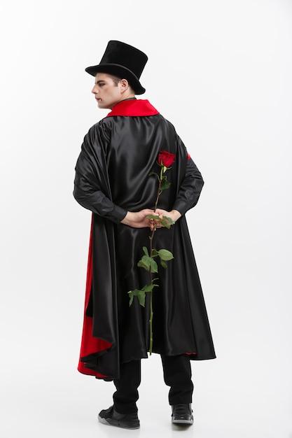 Il ritratto del vampiro caucasico bello che tiene rosso bello è aumentato sulla priorità bassa bianca dello studio. Foto Premium