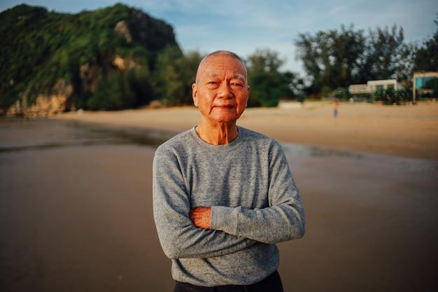 Il ritratto dell'uomo anziano senior si rilassa sul sorriso della spiaggia e sulla faccia felice Foto Premium