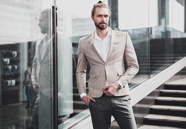 Il ritratto dell'uomo bello sexy si è vestito in vestito a quadretti beige elegante Foto Gratuite