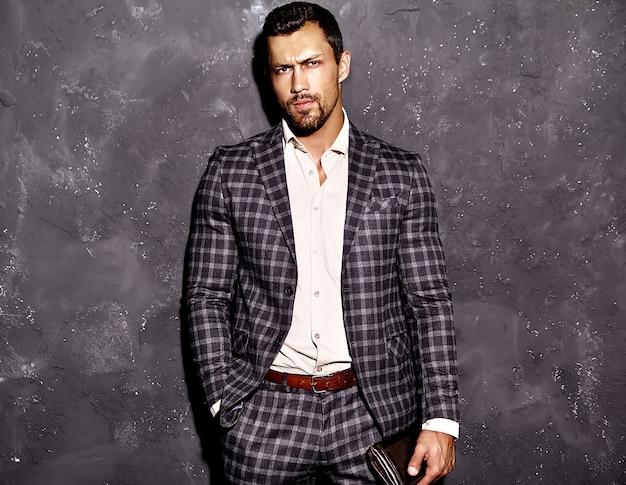 Il ritratto dell'uomo sexy di modello maschio di modo bello sexy si è vestito in vestito elegante che posa vicino alla parete grigia Foto Gratuite
