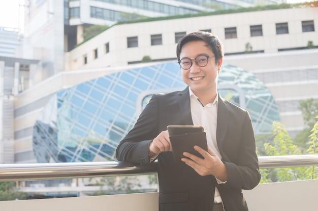 Il ritratto dell'uomo sorridente di affari sembra sicuro facendo uso della compressa del computer Foto Premium