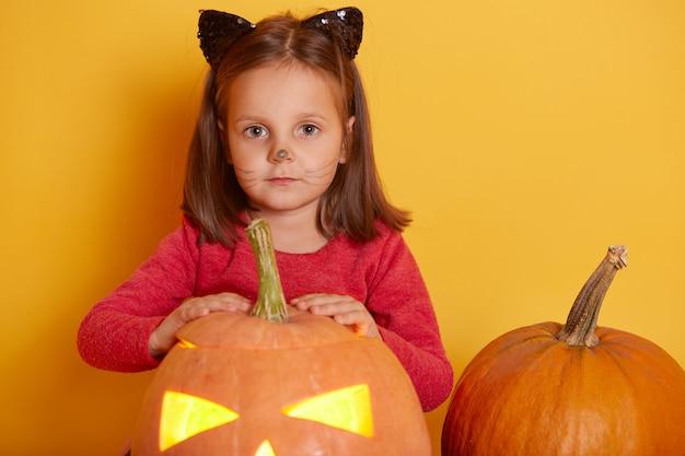 Il ritratto della bambina caucasica divertente adorabile ha vestito la camicia rossa con la zucca arancio di halloween. bambino che gioca, si diverte in studio per le vacanze di autunno. bambino che posa vicino alla zucca jack o lantern. Foto Premium