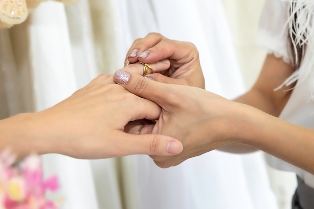 Il ritratto della coppia omosessuale asiatica mette su una fede nuziale. concetto lgbt lesbica. Foto Premium