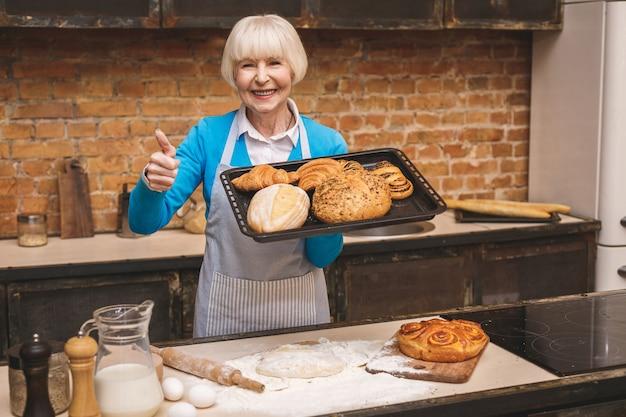 Il ritratto della donna invecchiata senior felice sorridente attraente sta cucinando sulla cucina. nonna che produce una cottura saporita. pollice su. Foto Premium