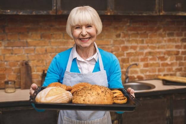 Il ritratto della donna invecchiata senior felice sorridente attraente sta cucinando sulla cucina. nonna che produce una cottura saporita. Foto Premium
