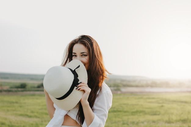 Il ritratto della ragazza asiatica spensierata affascinante dei capelli lunghi in vestiti bianchi e cappello di paglia gode della vita nel campo della natura Foto Premium