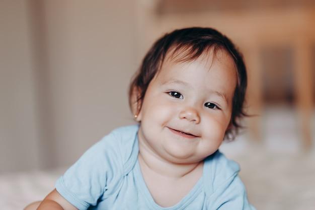 Il ritratto della ragazza corsa mista mista sveglia si trova sul letto Foto Premium