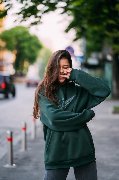 Il ritratto della ragazza sveglia con capelli lunghi esamina la macchina fotografica in città sul fondo della via. Foto Gratuite