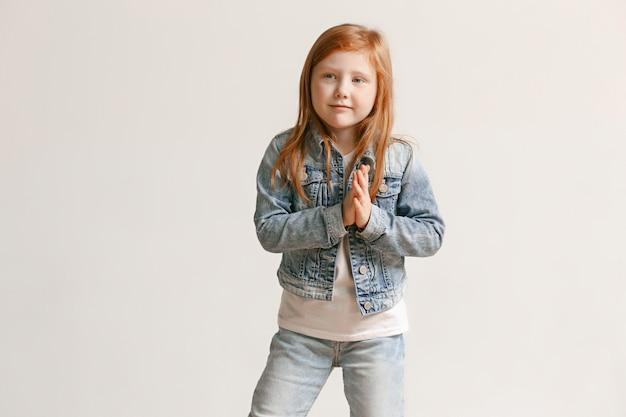 Il ritratto della ragazza sveglia del bambino in jeans alla moda copre l'esame della macchina fotografica e sorridere Foto Gratuite