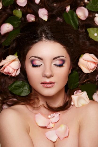 Il ritratto di bella donna castana con capelli ricci lunghi e trucco luminoso witjh fiorisce in capelli Foto Gratuite