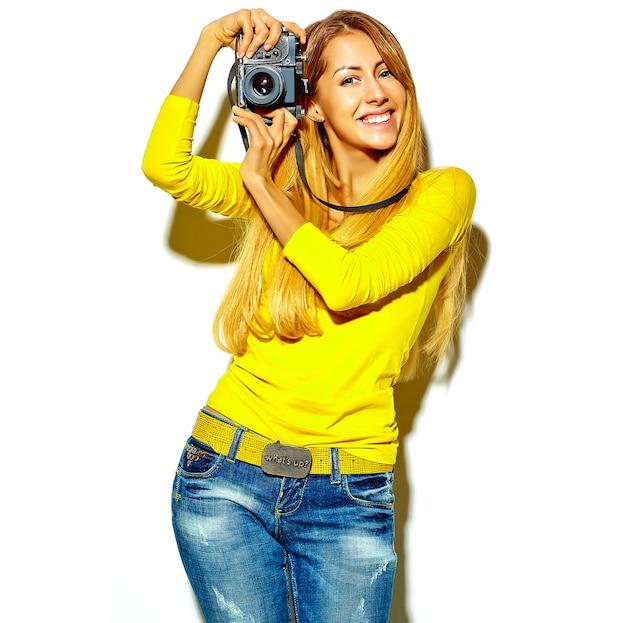 Il ritratto di bella ragazza bionda sorridente felice sveglia della donna in vestiti casuali dell'estate prende le foto che tengono la retro macchina fotografica, isolata su un bianco Foto Gratuite