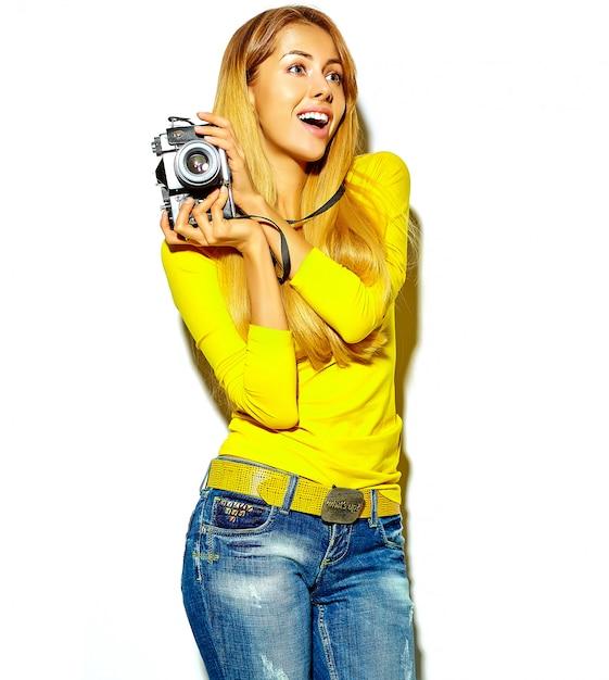 Il ritratto di bella ragazza bionda sorridente felice sveglia della donna in vestiti casuali dell'estate prende le foto che tengono la retro macchina fotografica Foto Gratuite