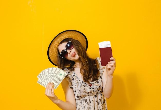 Il ritratto di bella ragazza felice del brunette che tiene i biglietti e il passaporto di viaggio delle banconote dei soldi Foto Premium