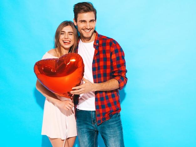 Il ritratto di bella ragazza sorridente e del suo ragazzo bello che tengono il cuore hanno modellato i palloni e la risata. coppia felice in amore. buon san valentino. posing Foto Gratuite