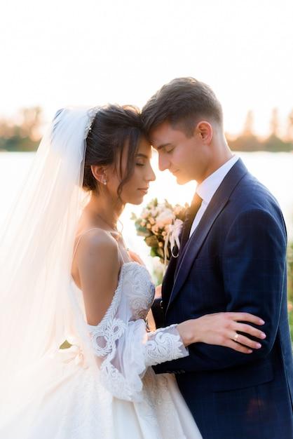 Il ritratto di bella sposa e sposo con gli occhi chiusi sta abbracciando vicino all'acqua all'aperto la sera Foto Gratuite