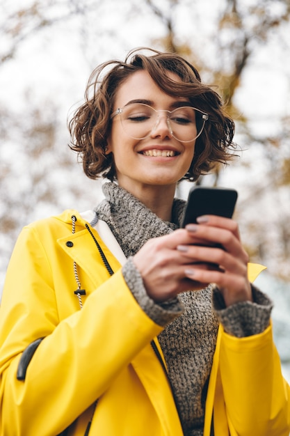 Il ritratto di bello messaggio di testo di battitura a macchina o di scorrimento femminile castana alimenta la rete sociale facendo uso del suo smartphone mentre è all'aperto Foto Gratuite