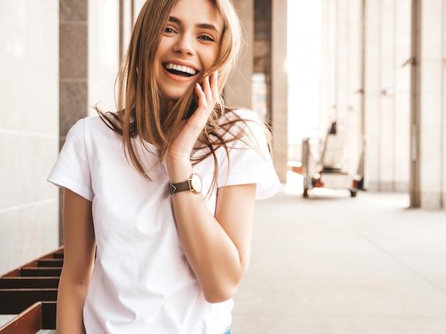 Il ritratto di bello modello biondo sorridente si è vestito in vestiti dei pantaloni a vita bassa dell'estate. Foto Gratuite