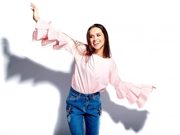 Il ritratto di bello modello sorridente caucasico della donna castana in blusa rosa luminosa e le blue jeans alla moda dell'estate con i fiori stampa Foto Gratuite
