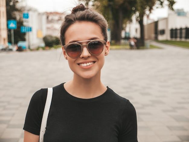 Il ritratto di bello modello sorridente si è vestito in vestiti dell'estate. ragazza d'avanguardia che posa nella via in occhiali da sole. divertimento donna divertente e positiva Foto Gratuite