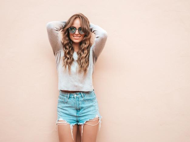Il ritratto di bello modello sorridente si è vestito in vestiti di shorts dei jeans dei pantaloni a vita bassa dell'estate Foto Gratuite