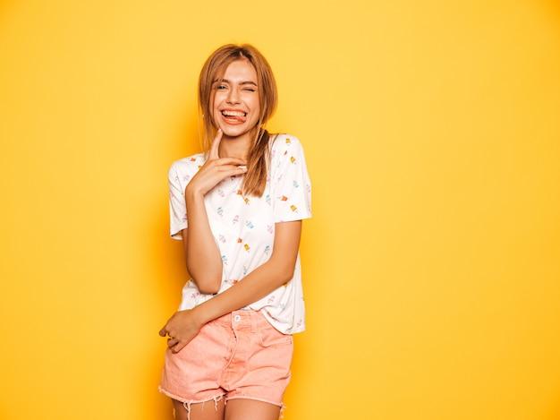 Il ritratto di giovane bella ragazza sorridente dei pantaloni a vita bassa negli shorts d'avanguardia dei jeans dell'estate copre. donna spensierata sexy che posa vicino alla parete gialla. modello positivo divertendosi e mostrando lingua Foto Gratuite