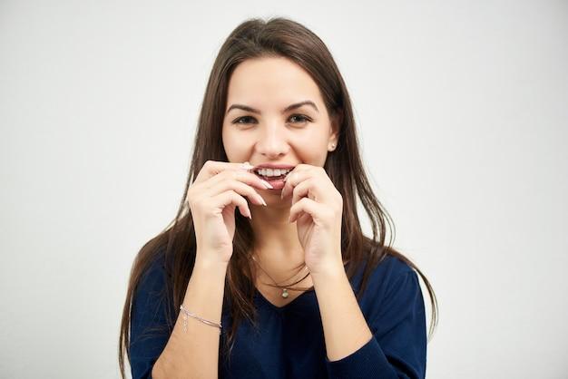 Il ritratto di giovane donna del brunette flosses i suoi denti con filo per i denti Foto Premium