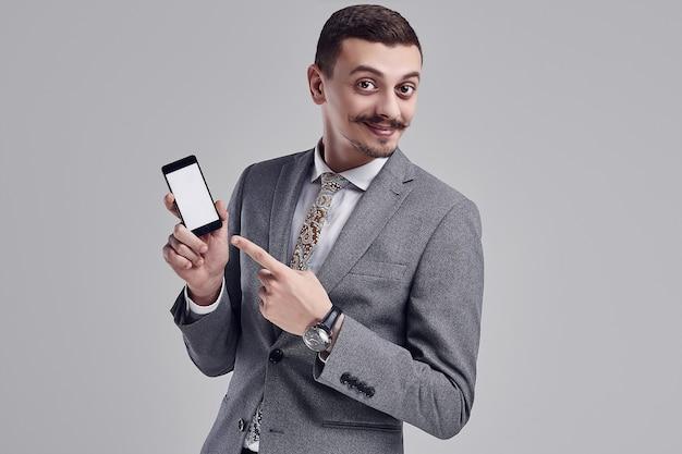 Il ritratto di giovane uomo d'affari arabo sicuro bello con i baffi operati nel vestito pieno grigio di modo indica il telefono sullo studio Foto Premium