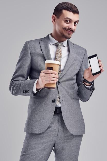 Il ritratto di giovane uomo d'affari arabo sicuro bello con i baffi operati nel vestito pieno grigio di modo tiene una tazza di caffè e un telefono sullo studio Foto Premium