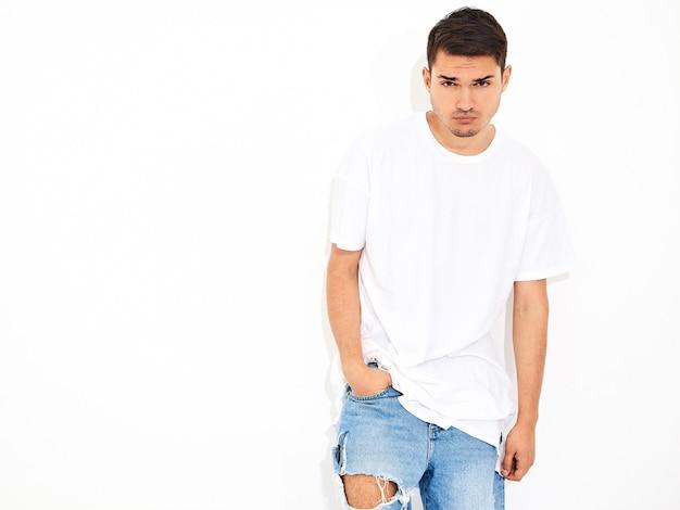 Il ritratto di giovane uomo di modello bello si è vestito nella posa dei vestiti e della maglietta dei jeans. braccia incrociate Foto Gratuite