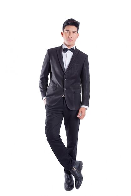 Il ritratto di giovane uomo sicuro asiatico si è vestito in smoking con il legame di arco isolato su priorità bassa bianca Foto Premium