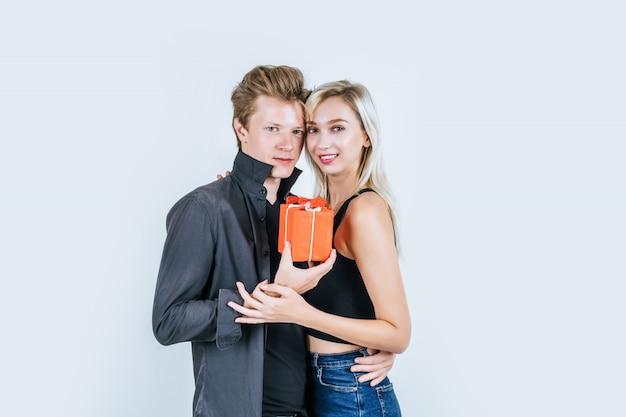 Il ritratto di giovani coppie felici ama insieme la sorpresa con il contenitore di regalo Foto Gratuite