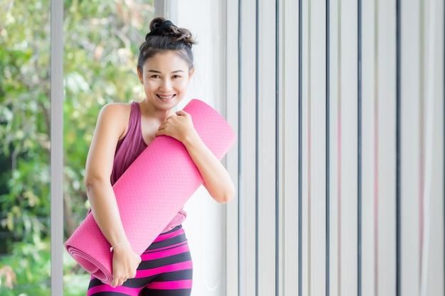 Il ritratto di un allenamento asiatico delle donne che pratica l'yoga in vestito rosa abbraccia la stuoia di yoga rotola il rosa e pratica lo stile di vita di benessere di meditazione e il concetto di forma fisica di salute in una palestra. Foto Premium