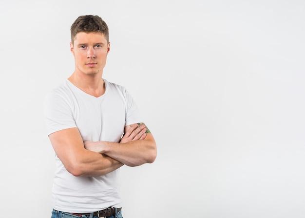 Il ritratto di un giovane con il suo braccio ha attraversato lo sguardo alla macchina fotografica contro fondo bianco Foto Gratuite