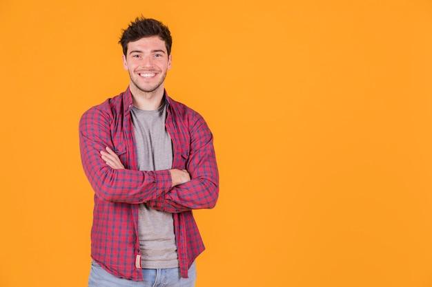 Il ritratto di un giovane sorridente con le sue armi ha attraversato l'esame della macchina fotografica Foto Gratuite