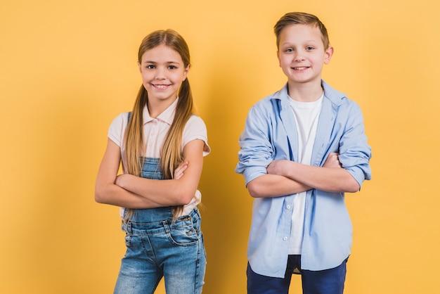 Il ritratto di un ragazzo e di una ragazza svegli felici con le loro armi ha attraversato guardando alla macchina fotografica Foto Gratuite