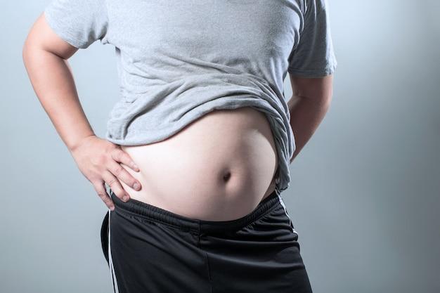Il ritratto di un uomo grasso asiatico mostra il suo corpo e la grande pancia. Foto Premium