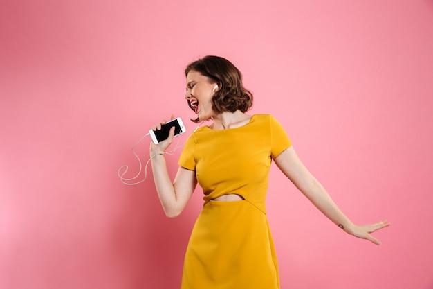 Il ritratto di una donna allegra in vestito e compone Foto Gratuite