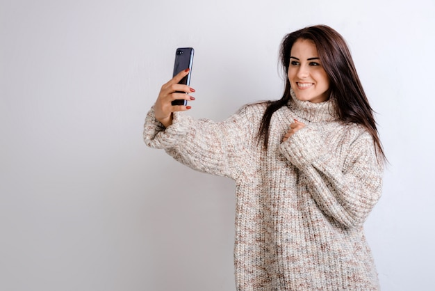 Il ritratto di una giovane bella ragazza alla moda del brunette fa i selfie in studio, si è vestita in un maglione caldo. Foto Premium