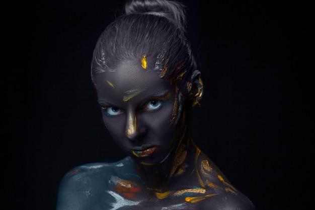 Il ritratto di una giovane donna che sta posando è coperto di pittura nera Foto Gratuite