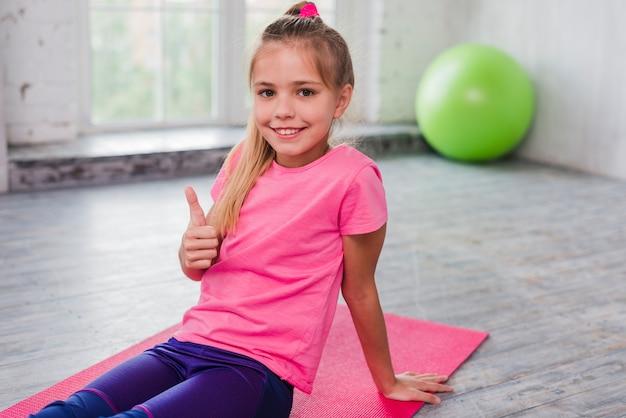 Il ritratto di una ragazza che si siede sull'esercitazione della stuoia che mostra i pollici aumenta il segno Foto Gratuite