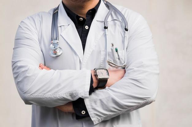 Il ritratto di uno stetoscopio maschio della tenuta di medico intorno al suo collo che sta con le armi ha attraversato contro il contesto bianco Foto Gratuite
