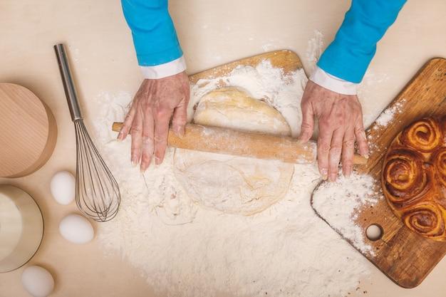 Il ritratto di vista superiore della donna invecchiata senior attraente sta cucinando sulla cucina. nonna che produce una cottura saporita. Foto Premium