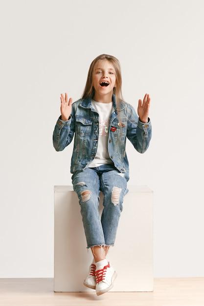 Il ritratto integrale di piccola ragazza teenager sveglia in jeans alla moda copre l'esame della macchina fotografica Foto Gratuite