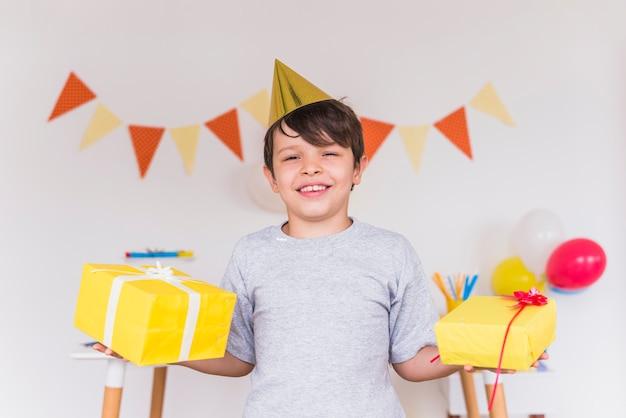 Il ritratto sorridente di un ragazzo che tiene i regali di compleanno in sua mano Foto Gratuite