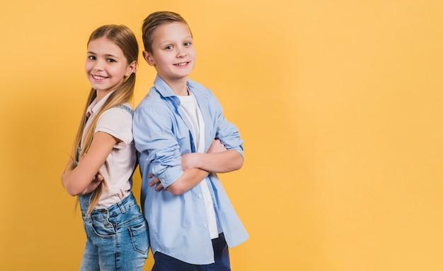 Il ritratto sorridente di una ragazza e di un ragazzo con il braccio ha attraversato la condizione di nuovo alla parte posteriore contro fondo giallo Foto Gratuite