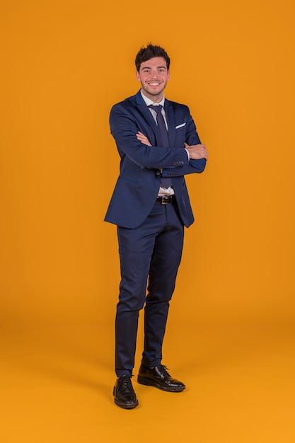 Il riuscito giovane uomo sorridente bello con il suo braccio ha attraversato la condizione contro un fondo arancio Foto Gratuite