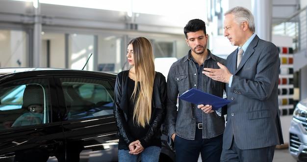 Il rivenditore di auto esalta le caratteristiche di un'auto per una coppia leggendo un documento Foto Premium