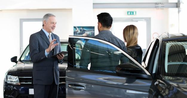Il rivenditore di auto esalta le caratteristiche di una macchina con una coppia utilizzando una tavoletta digitale Foto Premium