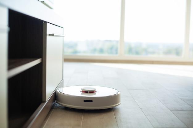 Il robot aspirapolvere funziona sul pavimento di legno in un salotto Foto Premium