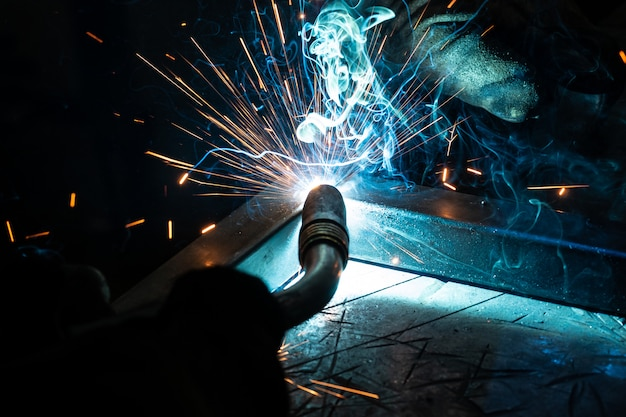 Il saldatore cucina il telaio. il saldatore cucina il metallo. il saldatore cucina strutture metalliche. lavori di saldatura scintille, metallo fuso Foto Premium